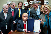 """United States President Donald J. Trump signs H.J. Res. 38, disapproving the rule submitted by the US Department of the Interior known as the Stream Protection Rule in the Roosevelt Room of the White House in Washington, DC on Thursday, February 16, 2017.  The Department of Interior's Stream Protection Rule, which was signed during the final month of the Obama administration, """"addresses the impacts of surface coal mining operations on surface water, groundwater, and the productivity of mining operation sites,"""" according to the Congress.gov summary of the resolution.<br /> Credit: Ron Sachs / Pool via CNP"""