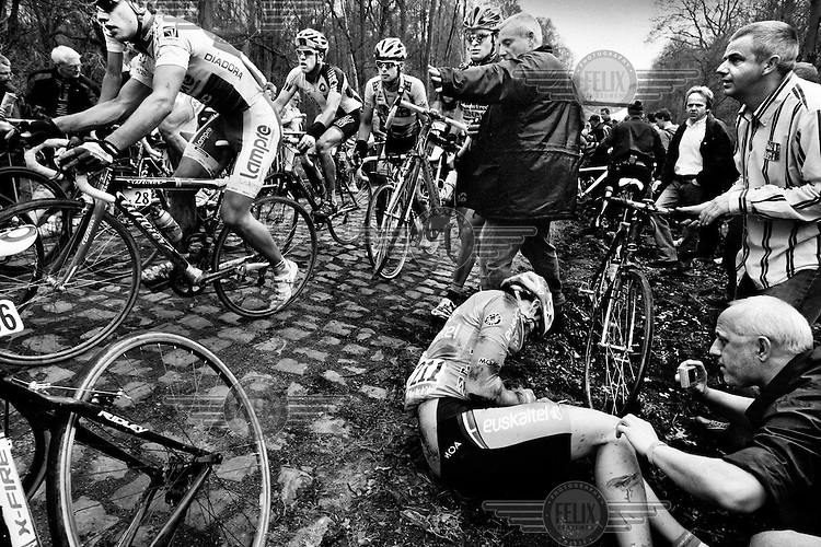 A participant lies hurt by the roadside, following a crash during the Paris - Roubaix cycle race (won by Tom Boonen). The Paris - Roubaix is one of the so-called classics of the racing calendar. Although affectionately known as the Queen of Races, it is notoriously tough, large sections being on slippery cobblestones..