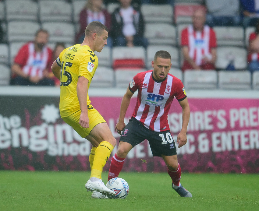 Lincoln City's Jack Payne vies for possession with Fleetwood Town's Paul Coutts<br /> <br /> Photographer Andrew Vaughan/CameraSport<br /> <br /> The EFL Sky Bet League One - Lincoln City v Fleetwood Town - Saturday 31st August 2019 - Sincil Bank - Lincoln<br /> <br /> World Copyright © 2019 CameraSport. All rights reserved. 43 Linden Ave. Countesthorpe. Leicester. England. LE8 5PG - Tel: +44 (0) 116 277 4147 - admin@camerasport.com - www.camerasport.com