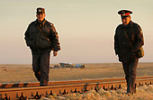 Russian security personnel walk the railroad line ahead of the Soyuz TMA-13 spacecraft as it is transported by railcar to its launch pad at the Baikonur Cosmodrome in Kazakhstan, Friday, Oct. 10, 2008 for launch Oct. 12 to carry Expedition 18 Commander Michael Fincke, Flight Engineer Yury V. Lonchakov and American Spaceflight Participant Richard Garriott to the International Space Station. The three crew members will dock their Soyuz to the International Space Station on Oct. 14. Fincke and Lonchakov will spend six months on the station, while Garriott will return to Earth Oct. 24, 2008 with two of the Expedition 17 crew members currently on the International Space Station.<br /> Mandatory Credit: Bill Ingalls / NASA via CNP