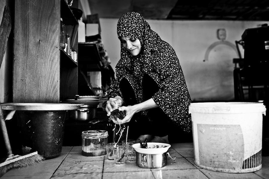Gaza, beach camp:  Shadi's wife doing her dishes in a room of an UNRWA school used as their home. <br /> <br /> Gaza, plage camp: La femme de Shadi fait ses plats dans une salle d'une &eacute;cole de l'UNRWA utilis&eacute;e comme leur maison.