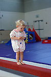 Albany, CA Girl, eighteen months old, balancing on balance beam at gymnastics program for preschool children. MR
