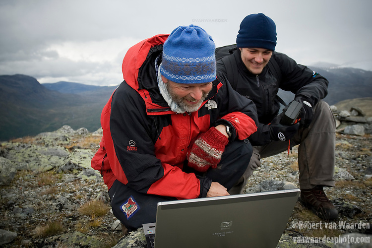 Bernd Etzelmuller, professor measures the temperature of the bore hole on his laptop while student Robert Way looks on.