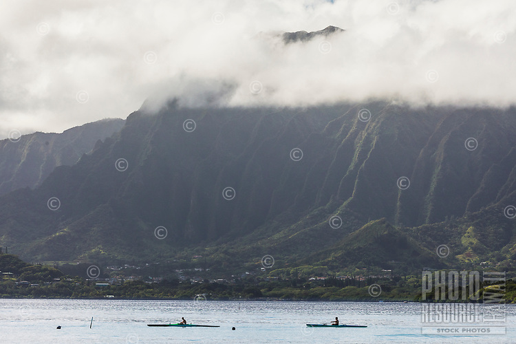 Paddlers in one-man canoes head further out to sea from Kane'ohe Bay, with the Ko'olau Mountains in the distance, Windward O'ahu.