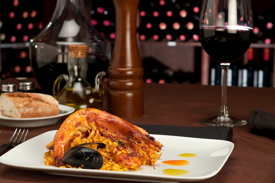 Tradition Seafood Spanish Paella in a restaurant table setting and wine cellar in the background.