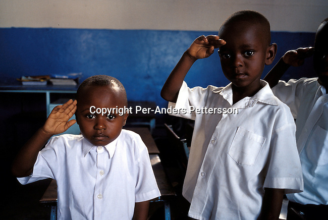 KINSHASA, CONGO - FEBRUARY 28: Mpoyo Dan, age 4, (left) during the singing of patriotic military song in his class on February 28, 2002 at ÒBambiniereÓ a school in Lingwala district, in Kinshasa, Congo. The teacher tells them about the occupation of Rwandan and Ugandan troops in the country..Photo: Per-Anders Pettersson/ Getty Images.....