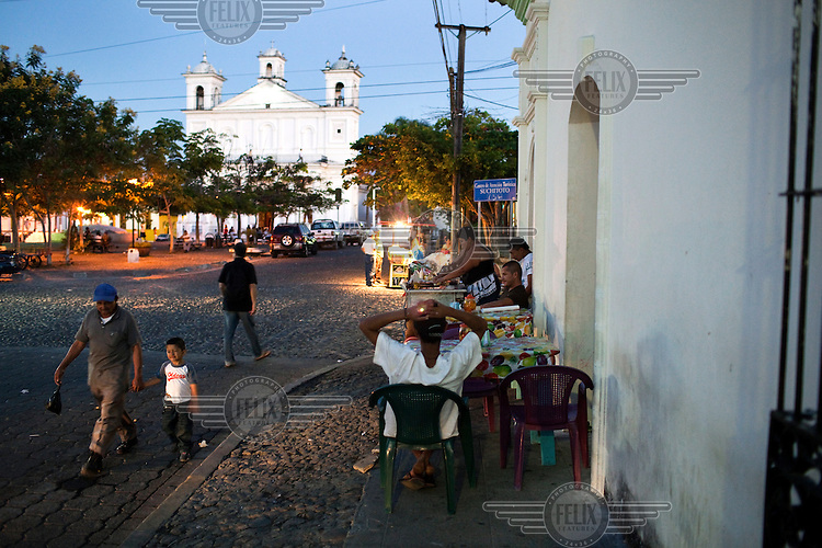 Street vendors plying their trade in the evening on the streets near the main church in Suchitoto.
