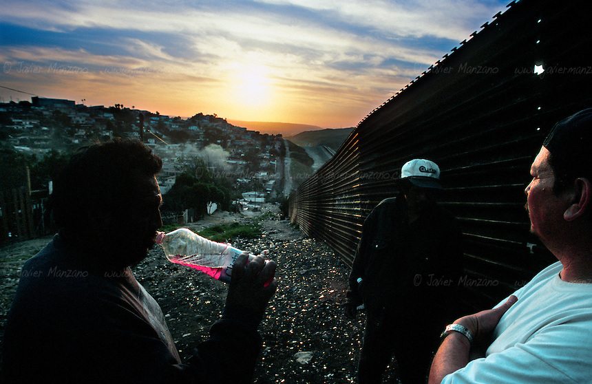 The Mexico/United States border runs for  1,969 miles (3,141 km), along rugged mountainous terrain, sparsely separated by a fence in populated areas, such as the Tijuana, San Diego border. It is here, where thousands of would-be migrants set up camp, building miles of shanty-towns along the border fence, as they become permanent settlers of this unclaimed turf. Many of them will try to cross, most of them will fail, forcing the flow of immigration to the more remote and dangerous sections along the border. The deserts of Arizona and Texas have become the main corridors for illegally entering the United States, resulting in dozens of deaths each year. ..Tijuana, Mexico. 03/19/04.
