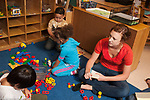 Education preschool 3-4 year olds psychology or education graduate student observing children play and making notes  horizontal