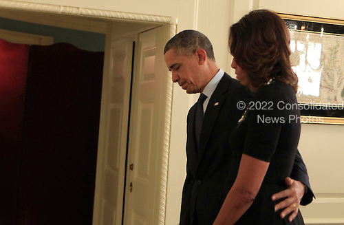United States President Barack Obama and first lady Michelle Obama participate in a candle lighting ceremony in the Map Room of the White House in Washington, D.C. on Saturday, December 14, 2013 to remember the 20 children and 6 adult school employees killed at the Sandy Hook Elementary School in New Town, Connecticut one year ago today.  <br /> Credit: Dennis Brack / Pool via CNP