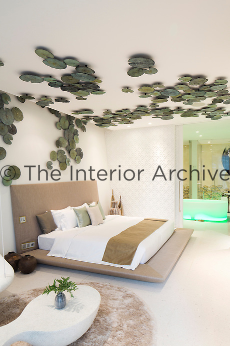 A generous platform bed in the Villa Siam at Iniala is positioned beneath a ceiling decorated with an artwork of lily pads