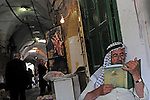 A man reads an Islamic book at the entrance to his shop, in a market in Hebron, West Bank.