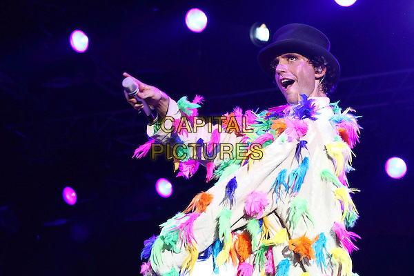 Mika (Michael Holbrook Penniman, Jr.).Live in concert - Moscow, Russia, .28th July 2010..half length music gig on stage feather boa microphone  white hat  mouth open funny .CAP/PER/SB.©SB/PersonaStars/Capital Pictures.