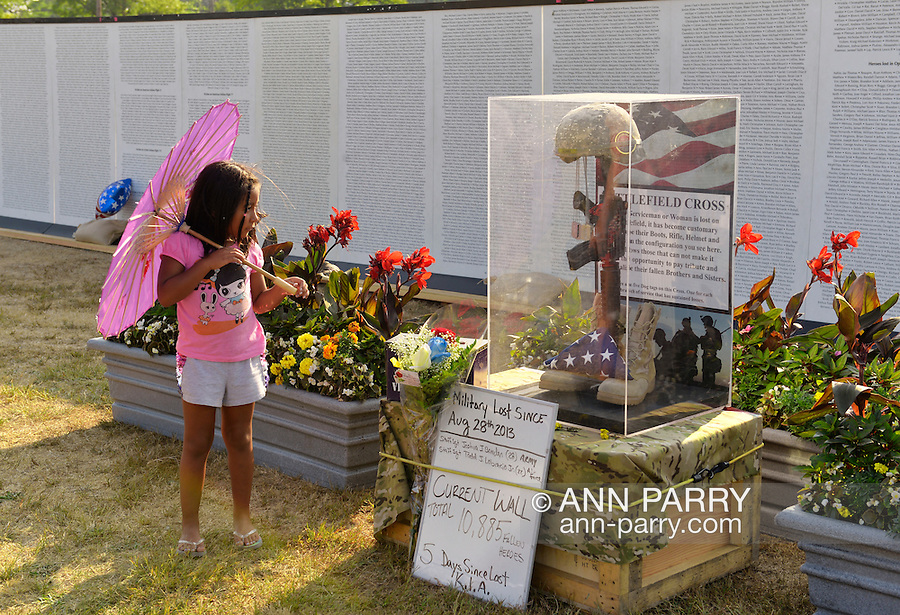 "East Meadow, New York, U.S. 11th September 2013. A young girl looks at the Battlefield Cross display in front of the Global War on Terror ""Wall of Remembrance"" a traveling memorial on display in New York for the first time, at Eisenhower Park on the 12th Anniversary of the terrorist attacks of 9/11. The unique 94 feet long by 6 feet high wall has, on one side, almost 11,000 names of those lost on September 11th 2001, along with heroes and veterans who lost their lives defending freedom of Americans over past 30 years."