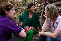 Pramila Tharu (center), 15, cradles her 2 year old toddler Prapti as she is interviewed by The Guardian's reporter Zoe Williams (left) and Save the Children's Global Head of Communications Ishbel Matheson in her fields in Bhaishahi village, Bardia, Western Nepal, on 29th June 2012. Pramila eloped and married at 12 and gave birth to Prapti at age 13. She delivered prematurely on the way to the hospital in an ox cart and her baby weighed only 1.5kg at birth. In Bardia, StC works with the district health office to build the capacity of female community health workers who are on the frontline of health service provision like ante-natal and post-natal care, especially in rural areas. Photo by Suzanne Lee for Save The Children UK
