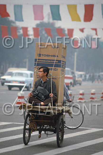 October 1984. In Beijing, a customer has chosen a Toshiba refrigerator made in Japan. Loaded on a rickshaw they are on his way home.