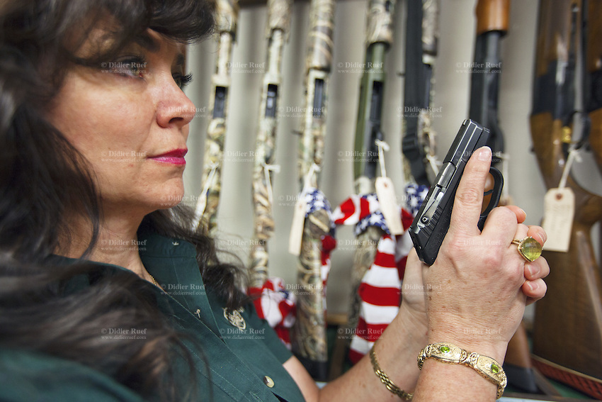 USA. Arizona state. Avondale town. Cheryl Todd is the owner and the manager of the gun shop AZFirearms.com with over 1'000 guns in stock. She stands behind the store's counter and holds in both hands her personal pistol, a Kel-Tec p-32. The Kel-Tec P-32 is a sub-compact semi-automatic pistol using the short-recoil principle of operation. Chambered in .32 ACP, it is popular for concealed carry in the United States; all edges are rounded and smoothed and nothing protrudes from the gun to get caught on clothing. A firearm is a portable gun, being a barreled weapon that launches one or more projectiles often driven by the action of an explosive force. Most modern firearms have rifled barrels to impart spin to the projectile for improved flight stability. The word firearms usually is used in a sense restricted to small arms (weapons that can be carried by a single person). The right to keep and bear arms is a fundamental right protected in the United States by the Second Amendment of the Bill of Rights in the Constitution of the United States of America and in the state constitutions of Arizona and 43 other states. 25.01.16 © 2016 Didier Ruef