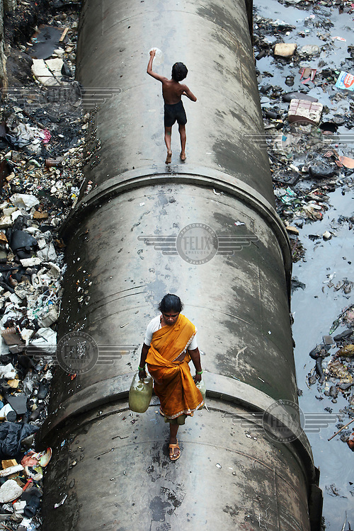 A boy and woman walking on a water pipe in a dump in Dharavi. Dharavi is India's biggest slum and home to more than a million people. The water pipe provides water to more affluent areas of Mumbai. In Dharavi people have very limited access to piped water and where it is available the flow often runs for a few hours each day. Slum dwellers frequently suffer from diseases attributed to poor water and sanitation facilities.