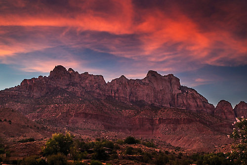 A fiery sunset lights up the sky at the West Temple at Zion National Park Utah