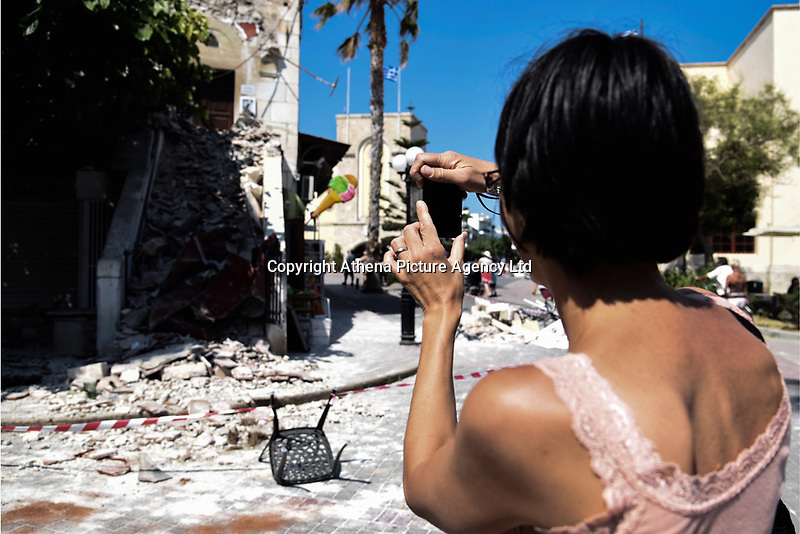 Pictured: A tourist takes a picture on her mobile phone of part of a building the old town that has suffered severe damage in Kos town, Greece.<br /> Re: A 6.4 Richter Scale earthquake has hit the tourist island of Kos in Greece.