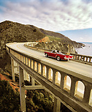 USA, California, Big Sur, couple on a road trip cross the Bixby Bridge in a 1965 Ford Mustang, Hwy 1