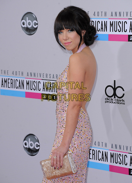 Carly Rae Jepsen.40th Anniversary American Music Awards - Arrivals held at Nokia Theatre L.A. Live, Los Angeles, California, USA..November 18th, 2012.AMA AMAs half length dress pink halterneck embellished jewel encrusted side looking over shoulder  clutch bag .CAP/DVS.©DVS/Capital Pictures.