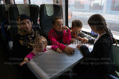 Illegal migrant family traveling to Germany sits on a train headed for Munich near Hegyeshalom (about 180 km West of capital city Budapest), Hungary on September 06, 2015. ATTILA VOLGYI