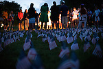 On Sept. 11, 2009, a field of tiny American flags flutter in the wind as people gather on Bascom Hill at the University of Wisconsin-Madison for the annual 9/11 Never Forget flag memorial and candlelight vigil to commemorate the thousands of lives lost in the 2001 terrorist attacks. The event was jointly hosted by the College Republicans and the College Democrats, both registered student organizations at UW-Madison.