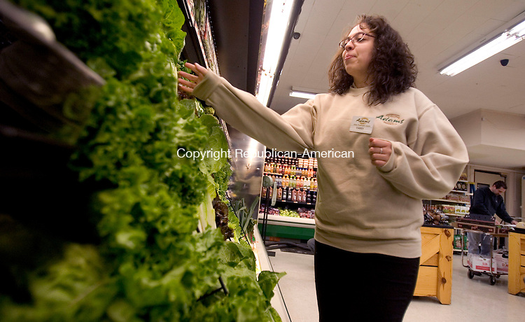 THOMASTON, CT. 23 March 2012-032612SV02-Yany Rosado gets the produce ready for customers at the new Adams Hometown Market in Thomaston Monday. The market opened in the place of the old Country Grocer on Main Street. The chain bought the independent grocery store last week and took a week making improvements. .Steven Valenti Republican-American
