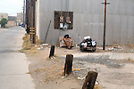 Homeless man sleeps in discarded chair behind a trash alley.(2)