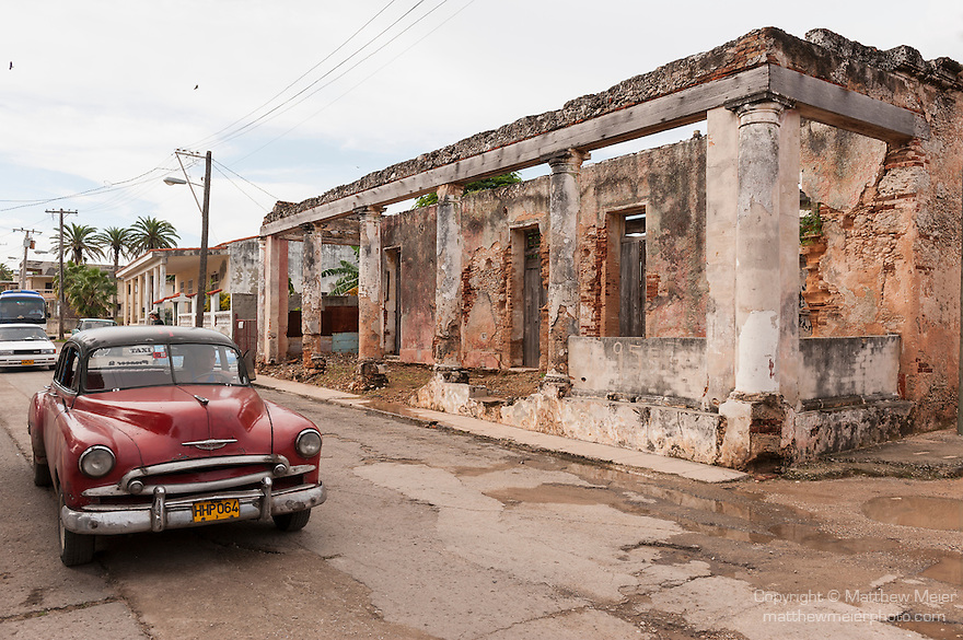 Cojimar, Cuba; a red, classic 1952 Chevy driving past a crumbling building down the street in Cojimar, the setting for Ernest Hemingway's The Old  Man and the Sea