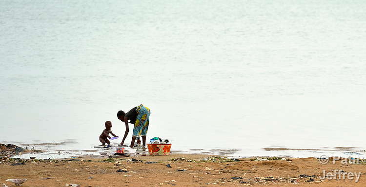 A woman and her child washing dishes in the Niger River at Segou, Mali.