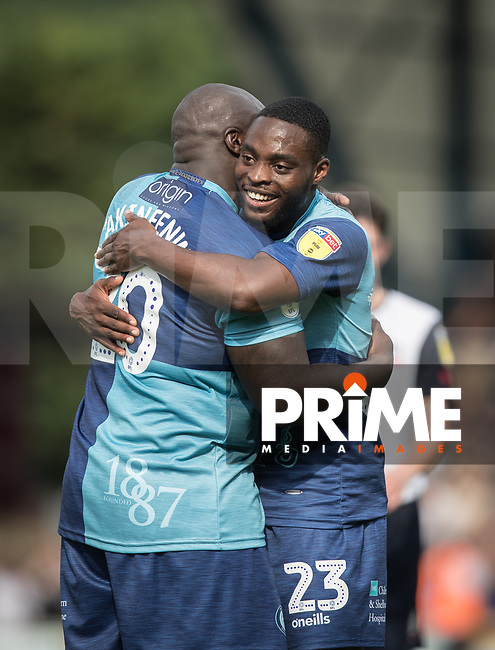 Fred Onyedinma of Wycombe Wanderers hugs Adebayo Akinfenwa of Wycombe Wanderers during the Sky Bet League 1 match between Wycombe Wanderers and Bolton Wanderers at Adams Park, High Wycombe, England on 3 August 2019. Photo by Andy Rowland.