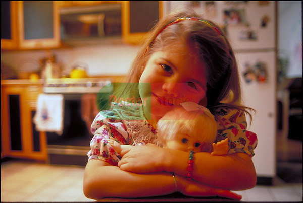young smiling girl holding toy doll in kitchen