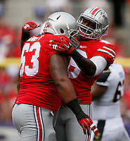 Ohio State Buckeyes defensive lineman Steve Miller (88) embraces Ohio State Buckeyes defensive tackle Michael Bennett (63) after a play during Saturday's NCAA Division I football game against the Navy Midshipmen at M&T Bank Stadium in Baltimore on August 30, 2014. (Dispatch Photo by Barbara J. Perenic)
