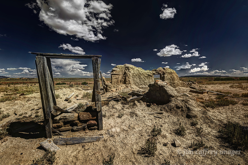 An eroded, abandoned adobe ruin and wooden frame near the small village of San Luis along Sandoval County Road 278 in the Rio Puerco Valley in the San Juan Basin in northwestern New Mexico.
