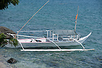 Anilao, Philippines; a Banca, or outrigger boat, is anchored along shore in the early morning