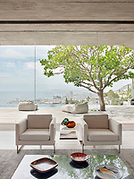 The contemporary home has a relaxed, peaceful quality with a seamless connection between indoor and outdoor living. Concrete is used in the ceilings and walnut wood floors add warmth. The floor to ceiling windows make the most of the spectacular view.