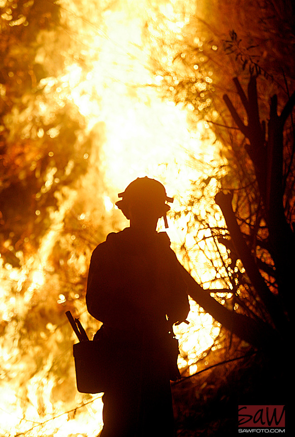 LOS ANGELES,CA - SEPTEMBER 22,2009:  A firefighter watches a backfire set to protect a ranch along Grimes Canyon Road Tuesday evening, September 22, 2009. After burning over 6000 acres, winds calms, giving firefighters a chance to set backfires to protects homes in the path of the fire. (Spencer Weiner/Los Angeles Times)