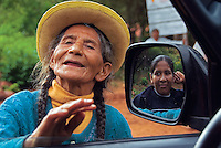 An elderly Bolivian woman has a passing conversation with a friend in a car.