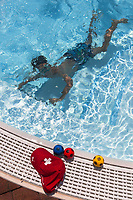 Switzerland. Canton Ticino. Tenero. Camping Campofelice. A young boy is diving underwater in the swimming pool. On the pool's edge, three colorful balls and a red cap from the Credit Suisse with the swiss flag. The flag of Switzerland consists of a red flag with a white cross (a bold, equilateral cross) in the centre. It is one of only two square sovereign-state flags. Credit Suisse Group AG is a Swiss multinational investment bank and financial services company founded and based in Switzerland. 20.07.2018 © 2018 Didier Ruef