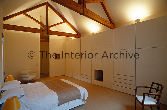 Uplighters have been used to create a dramatic effect in this minimalist bedroom with wooden roof beams