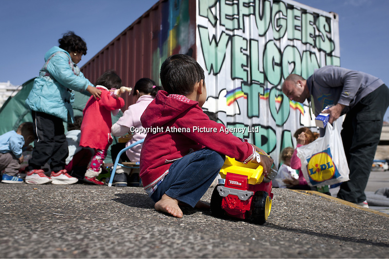 Pictured: Young children are handed out toys  Monday 07 March 2016<br /> Re: Migrants have been gathering at the port of Piraeus, near Athens, Greece.