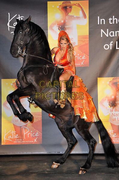 Katie Price (Jordan) and Dante the Horse.Katie Price launches her eighth novel on horseback, 'In The Name of Love', at The Worx Studios, London, UK. Today is a dream come true for Katie Price as she presented the book astride one of her childhood bedroom pin-ups, a rearing Lloyds Bank Black stallion, London, England..June 21st, 2012.full length orange dress sitting riding train gown gold boots side hat halterneck red.CAP/BF.©Bob Fidgeon/Capital Pictures.