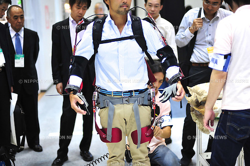 October 17, 2012, Tokyo, Japan - Visitor tries Muscle Suits by Tokyo University of Science during Japan Robot Week 2012 at the Tokyo Bigsight. It helps people to carry a heavy thing easier. This exhibition is held to showcase new robots and high technology equipments for visitor. Japan Robot Week 2012 runs from October 17 - 19. (Photo by Yumeto Yamazaki/AFLO)