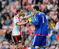 John O'Shea of Sunderland (left) gets into a heated debate with goalkeeper Costel Pantilimon of Sunderland over defensive duties during the Barclays Premier League match between Sunderland and Swansea City played at Stadium of Light, Sunderland