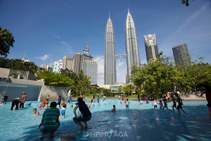 Malaysia, Kuala Lumpur. Petronas Twin Towers, the tallest buildings on Earth from 1998-2004 (still the tallest twin buildings) towering over the childrens' playground at Kuala Lumpur City Centre Park.