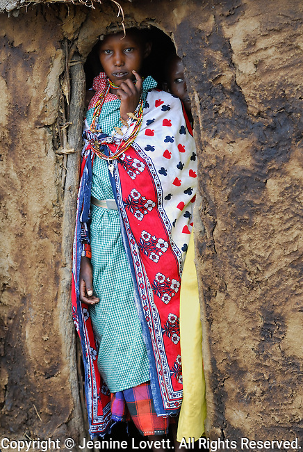 Maasai child peering threw doorway of mud hut.
