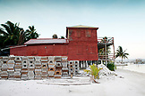 BELIZE, Caye Caulker, old traps are stacked by a boarded up building by the sea