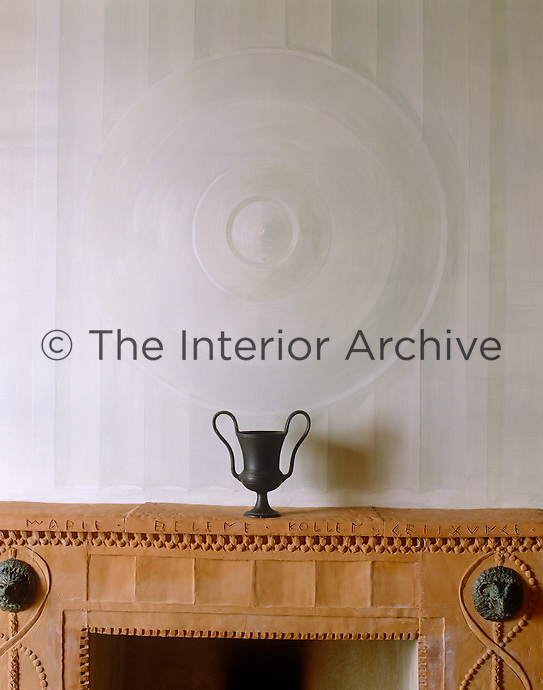 A dining room wall is decorated with a trompe l'oeil medallion above a Roman-inspired terracotta fireplace displaying a single black antique urn